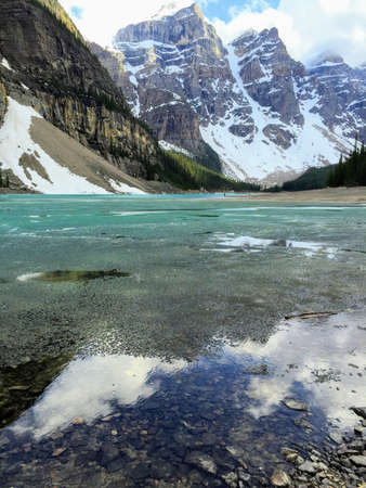 A view looking over Moraine Lake, in Jasper National Park, Alberta, Canada.  The sun is peaking through the grey clouds and illuminating the partially frozen turquoise lake below. 版權商用圖片