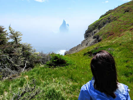 Female tourist admiring an incredible iceberg floating along the rugged coast beside the Skerwink Trail in Newfoundland and Labrador, Canada 免版税图像