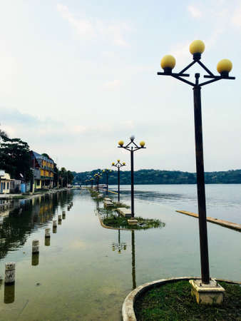 Flores, Guatemala - May 24th, 2018: The boardwalk of Flores, Guatemala overrun by rising waters, potentially highlighting the impacts of climate change and rising water levels.