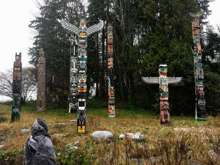 Vancouver, Canada - December 26th, 2016: A young tourist admires the totem poles in Stanley Park on a chilly Boxing Day in Vancouver, Canada.