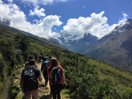 Cusco Province, Peru - May 8th, 2016: A young group of international hikers, led by their local Inca guide, navigate the Andes mountains on the Salkantay Trail towards Machu Picchu. 新闻类图片