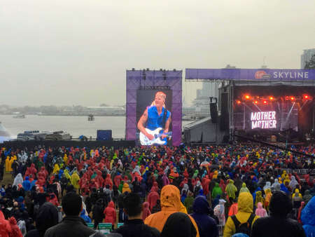 Vancouver, Canada - September 9th, 2018: A big crowd watches Mother Mother on a rainy Sunday afternoon at the Skookum Music Festival with Coal Harbour and the Vancouver skyline in the background