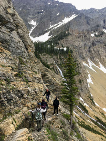 Hiking the rocky terrain of the Crypt Lake Trail, a steep ascent to Crypt Lake including walking a long the very edge of a mountain.  The hike is in Waterton Lakes National Park in Alberta, Canada Editorial