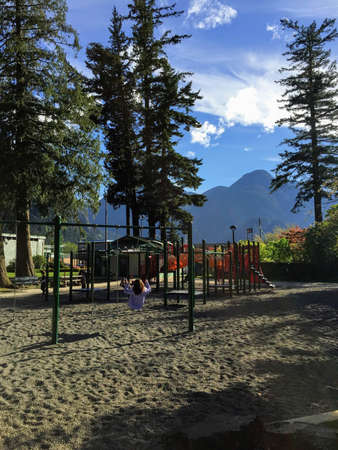 A young traveller on the swings on an empty playground in Hope, British Columbia, Canada