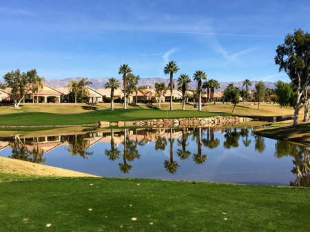 A beautiful view from the tee box of a difficult par 3 that requires a shot over the water onto an island green.  Palm trees are behind the green and reflect on the water.  Great golf in Palm Springs.