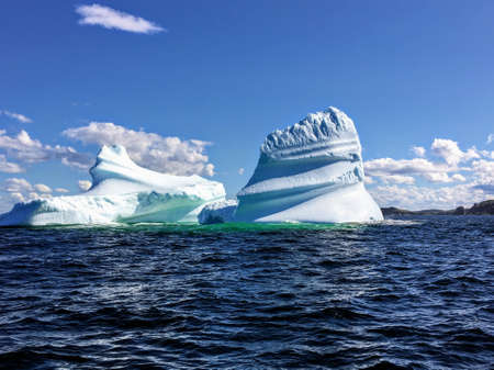 A massive iceberg floating off the coast of Twilingate, Newfoundland and Labrador, Canada.  The iceberg floats in the vast open ocean and flowed down from the arctic. 免版税图像
