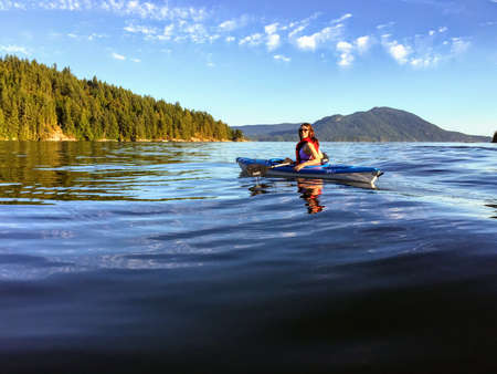 A girl enjoying kayaking on the beautiful and calm ocean waters of Howe Sound, off of Gambier Island, British Columbia, Canada.  A fun activity to do on a lovely summer evening.