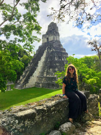 A pretty young female tourist posing in front of the Tikal ruins, ancient Mayan ruins deep in rainforests of northern Guatemala. Stock Photo
