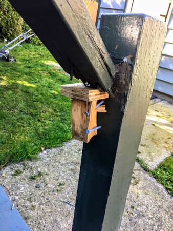 An example of poor craftsmanship on display on the railing of a wooden staircase.  The staircase railing  is falling a part and the railing has been poorly nailed into the fence post