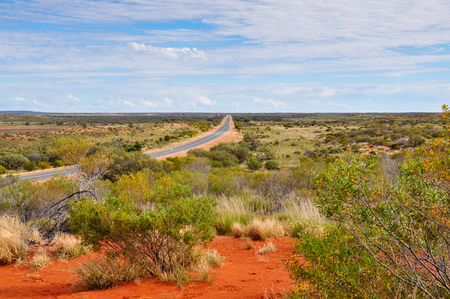A long straight road disappearing into the distance in the Norther Territory in Australia