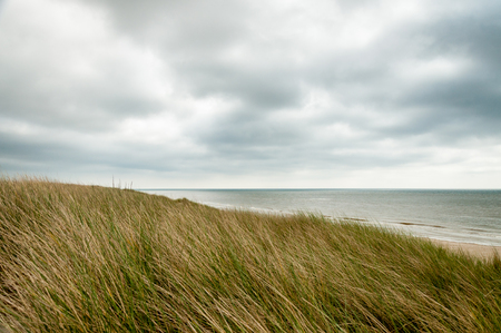 A grassy hill looking out over a cloudy sea in Northern France