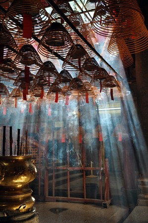 Light pouring into a temple through the incense smoke in Hong Kong