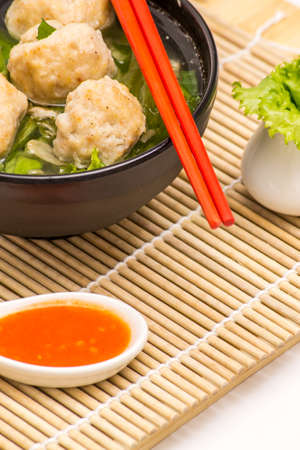 Fish meatball soup top of bamboo mat with chopstick