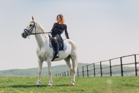Young woman in black dress with her white horse outdoor
