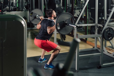 Strong man in the gym doing squats