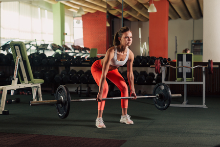Young fit woman doing a deadlift legs exercise in the gym
