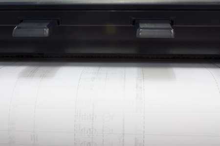 A CAD plotter printing a drawing shot from the front photo