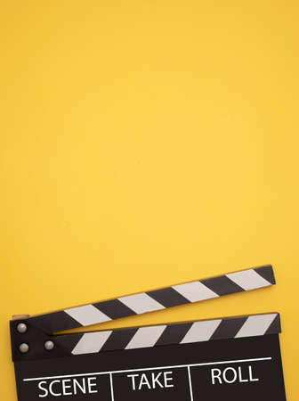 Film clapperboard on yellow background. Entertainment concept.