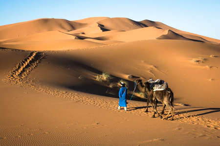 Camel men crossing the Sahara desert wearing traditional clothes