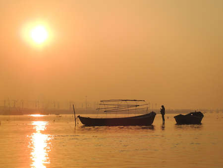 spiritualism: Sunrise at Ganges river with lonely boatman in Allahabad, India Stock Photo