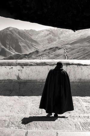Buddhist monk walking down the stairs of the Tibetan monastery.