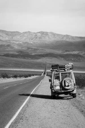 endless road: Traveler stopped on the middle of an endless road somewhere in the California desert.