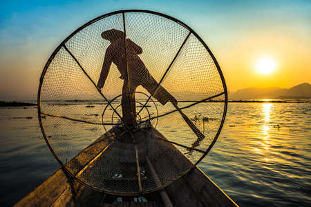 Sunset with a traditional boatman paddling in Inle Lake, Myanmar