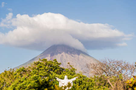 Ometepe, Nicaragua. February 2018. A view of the Volcano Concepcion with a religious icons in the foreground on ometepe island in Nicaragua.