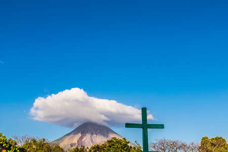 Ometepe, Nicaragua. February 2018. A view of the Volcano Concepcion with a religious icons in the foreground on ometepe island in Nicaragua. Editorial