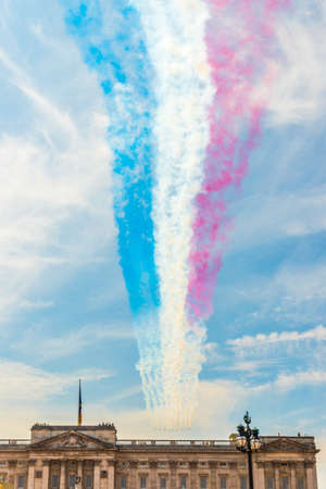 London. June 9 2018. A view of the red arrows team and the colored smoke they trail as they fly over Buckingham Palace during the Queens birthday celebrations of Trooping the Colour Editorial