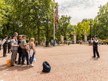 伦敦。2018年6月9日。一名警官在女王生日庆典上为游客拍照