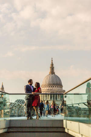 London. June 2018. A view of a couple posing on millenium bridge with st pauls in the background.