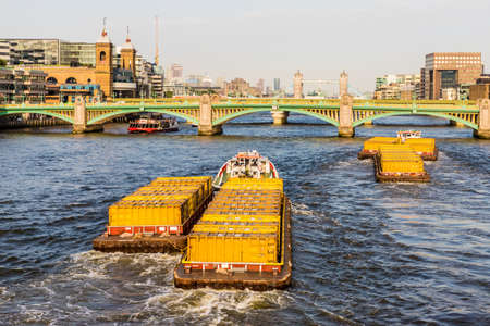 London. June 2018. A view of cargo tugs on the ruiver thames in London.