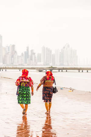 Panama City, Panama. March 2018. A view of colorfully dressed Kuna Yala women against the city skyline in Panama City in Panama