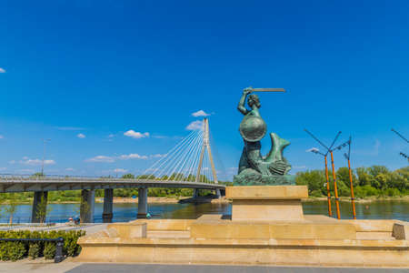 Warsaw Poland. April 2019. A view of the Syrenka of Warsaw Mermaid Statue and the Swietokrzyski Bridge by the Vistula River in Warsaw in Poland Editöryel