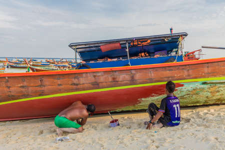 Ko Lipe Thailand. A view of a local man painting long tail boats on Ko Lipe in Thailand