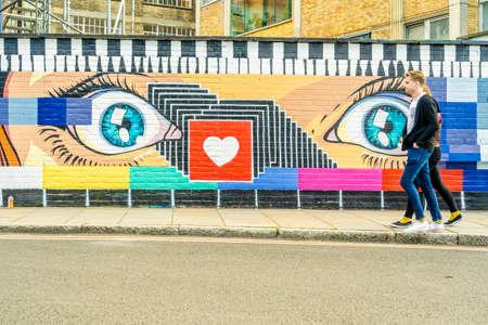 People walking past Street art in Shoreditch, London, England, Uk, Europe