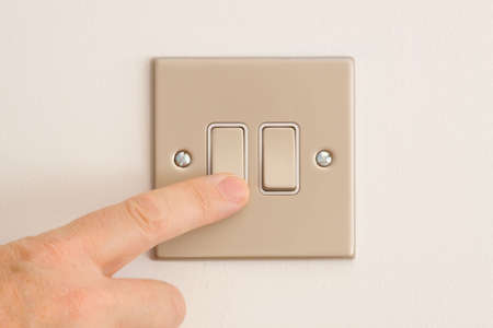 save energy: British Double Lightswitch on a White Wall in off position about to be pressed