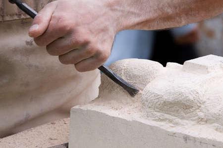 Close up di uno scultore sul luogo di lavoro al lavoro su un blocco di pietra arenaria