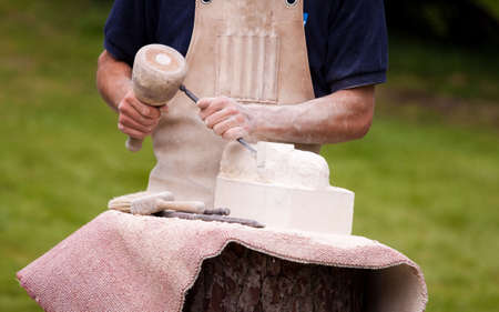 chisel: Sculptor working a block of stone with a chisel