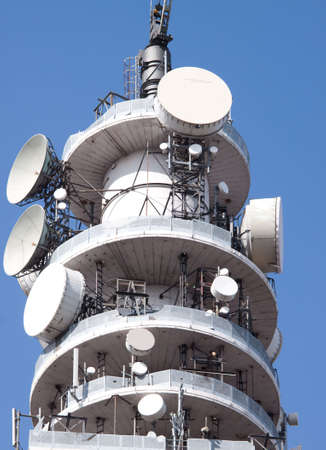 Telecom tower with multiple receiving and transmitting dishes against a blue sky Stock Photo - 5732779