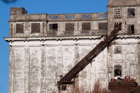 ravaged: Facade of a derelict factory building with brocken windows and crumbing concrete Stock Photo