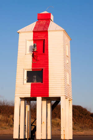 Wooden lighthouse built out of oak on the sandy beach at Burnham-on-Sea at sunset. Stock Photo