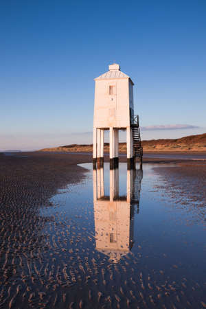 Wooden lighthouse built out of oak on the sandy beach at Burnham-on-Sea at sunset. Th structure is reflected in a tidal pool. photo