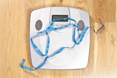 Modern electronic scales with blue tape measure across it on a wooden floor symbolising dieting Stock Photo - 6681686