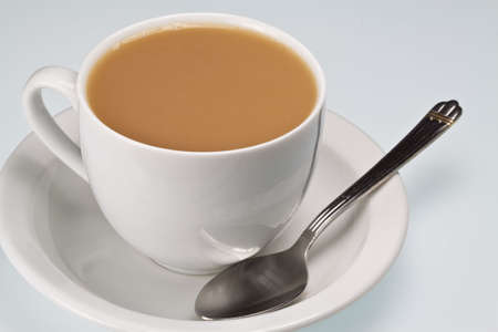 White china cup of tea with milk and teaspoon on a plain background