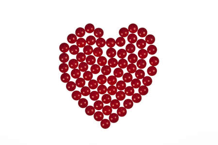 Heart shape created out of red tablets on a white background symbolising heart medication or romance and valentines day valentines day photo