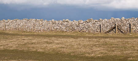 drystone: Sunlit drystone wall and barb wire fence against grey cloud