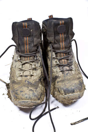 Pair of muddy , worn walking or hiking boots on a plain background Stok Fotoğraf