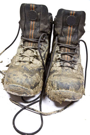 muddy clothes: Pair of muddy , worn walking or hiking boots on a plain background Stock Photo